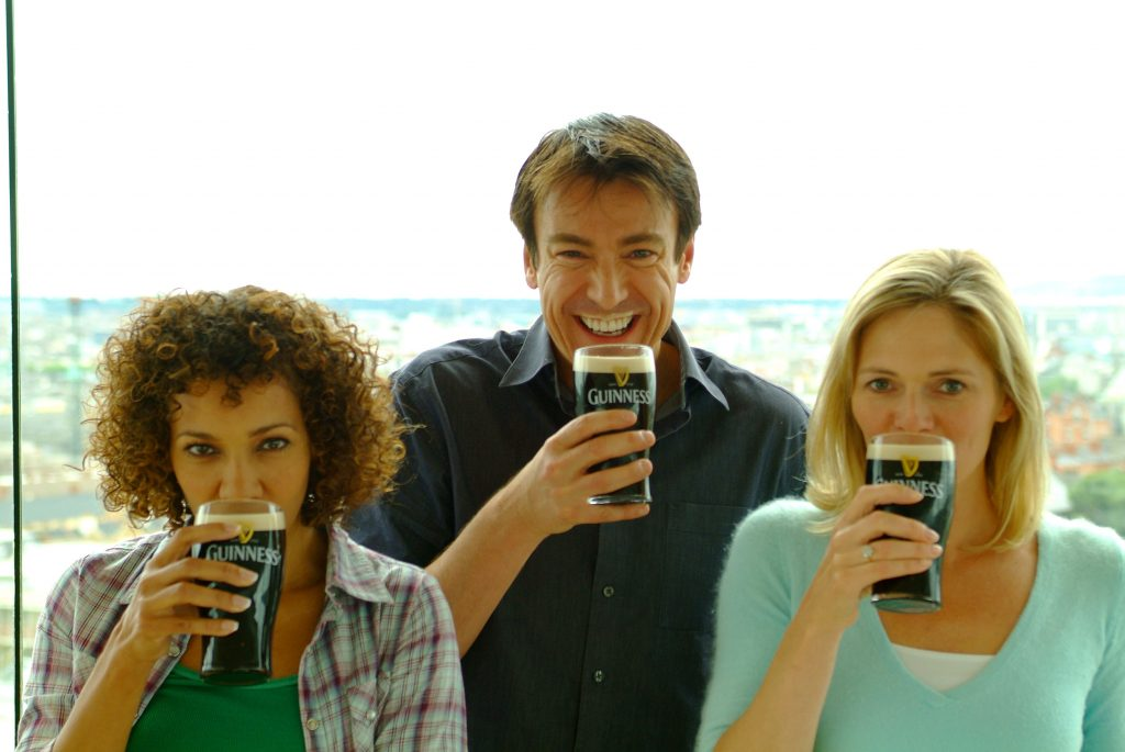 Friends sipping pints, man with pint moustache in the Gravity Bar, Guinness Storehouse, madly