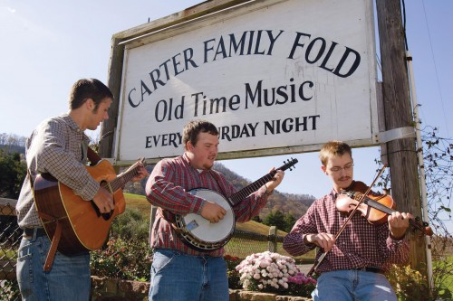 Bluegrass musicians play in front of the sign of the Carter Family Fold.