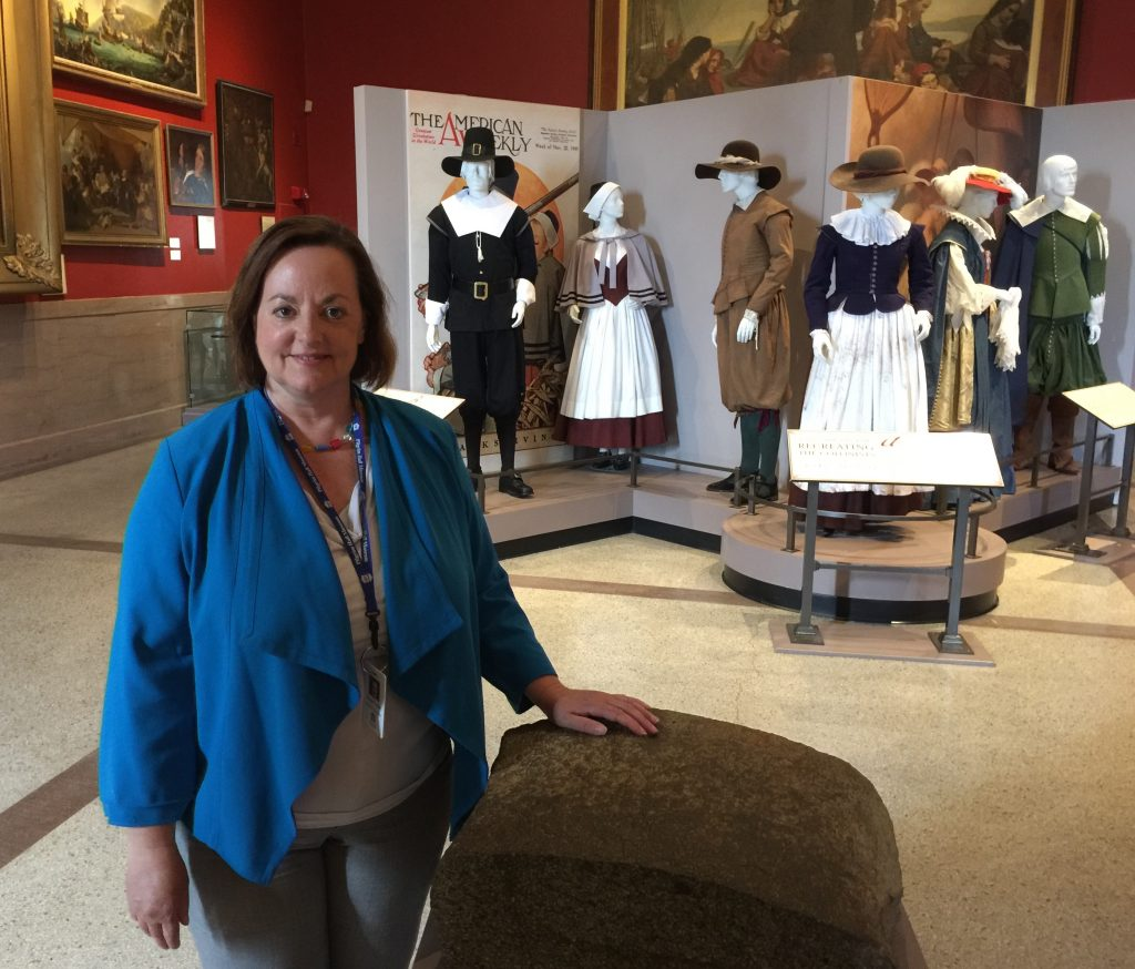 Group Tour and Marketing Manager Denise Giblin with Piece of Plymouth Rock, Image Courtesy of Pilgrim Hall Museum, Plymouth Massachusetts.
