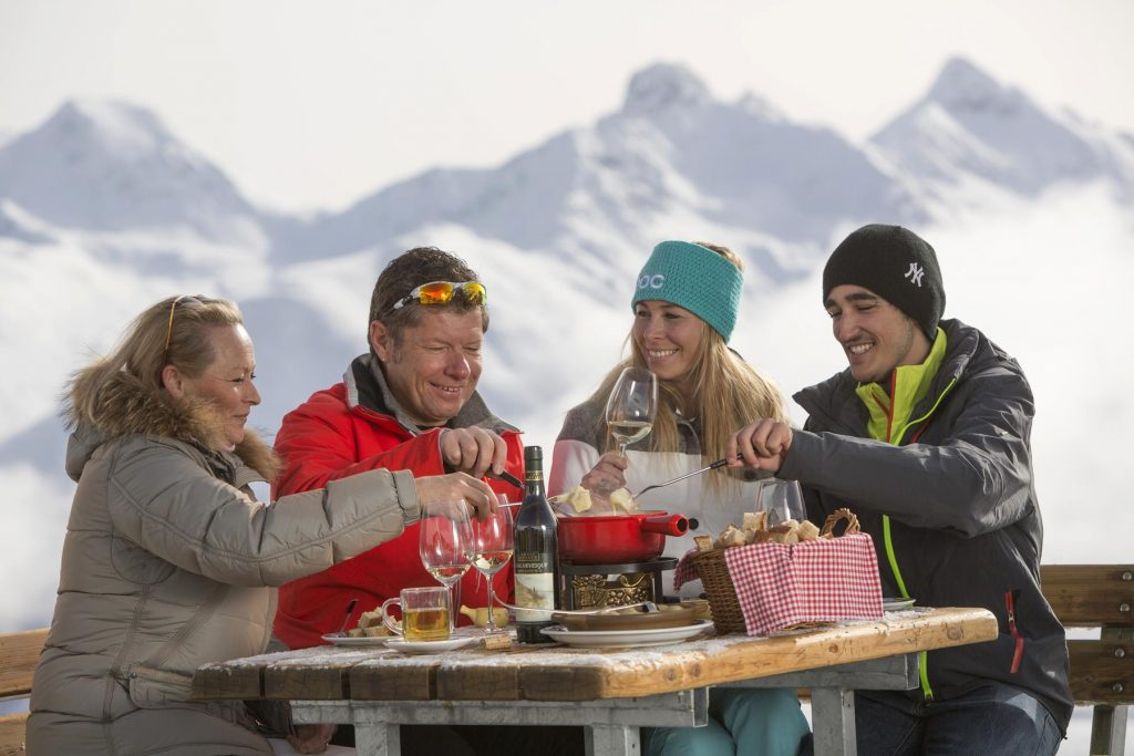 A party of four enjoys Fondue on the sun terrace of the Glunetta Restaurant in Celerina-Marguns.