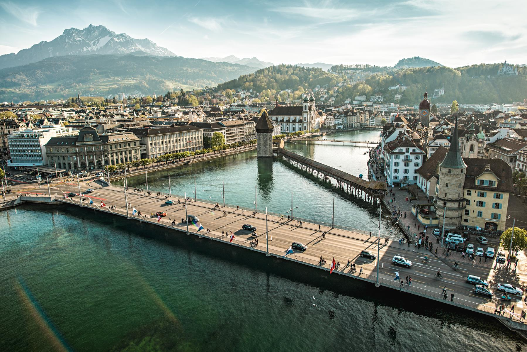 The covered Chapel Bridge and its tower are symbols of Lucerne. Mt. Pilatus looms in the distance. Switzerland Tourism