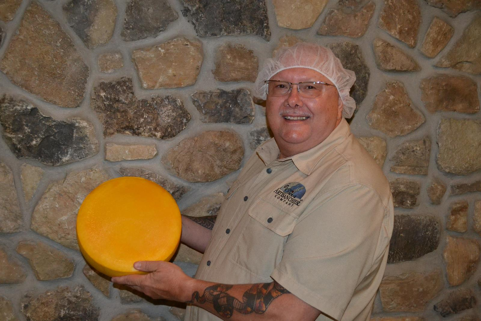 Mike Brennenstuhl, owner of Glacier Ledge and Door Artisan Cheese Co. in Egg Harbor shows one of his many cheeses his firm creates