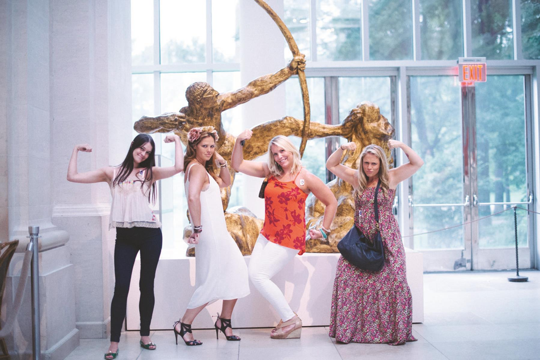 A bachelorette party poses with the art