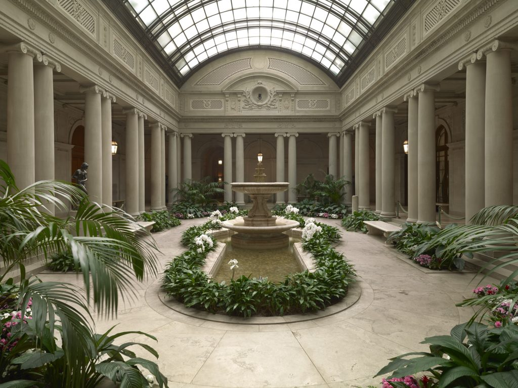 The Garden Court was designed by John Russell Pope to replace the open carriage court of the original Frick residence. The Court's paired Ionic columns and symmetrical planting beds were echoed in Pope's later designs for the original building of the National Gallery of Art in Washington, D.C.