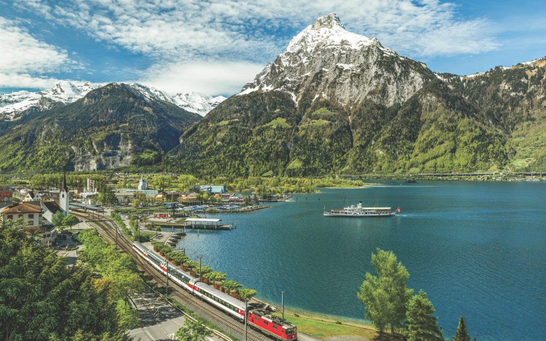 In the Lake Lucerne town of Flüelen, Gotthard Panorama Express passengers change from the boat to the train, or vice versa. The rail-boat journey between Lucerne and Lugano takes 5½ hours. ©: Gotthard Panorama Express in Flüelen, Switzerland @Swiss Travel System, 2022